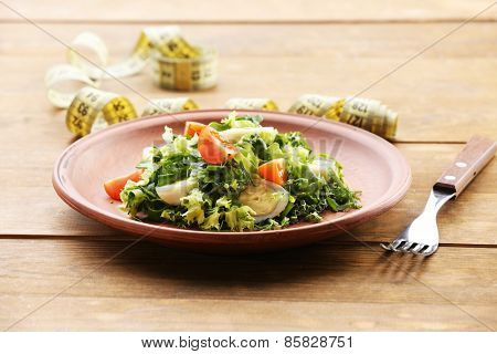Salad with quail egg and basil in plate on rustic wooden table background