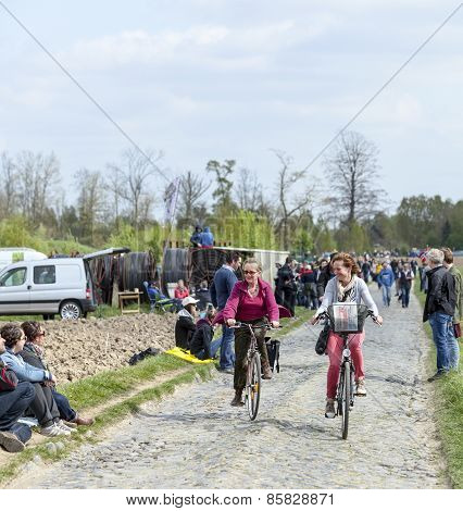 Two Casual Women Cycling On A Cobblestoned Road