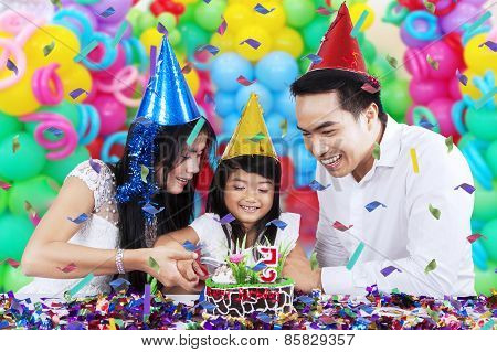 Little Girl Cutting Birthday Cake With Parents