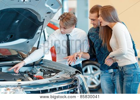 Sales consultant shows technical characteristics of the vehicle