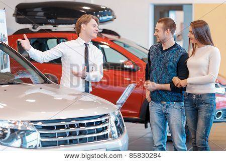 Customers communicate with sales consultant about the car