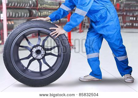 Technician Changing A Tire At Workshop