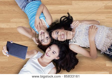 Teenage Girls Lying Down And Taking Photo