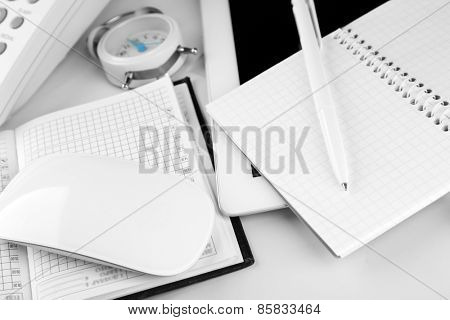 Office workplace with alarm clock and tablet close up