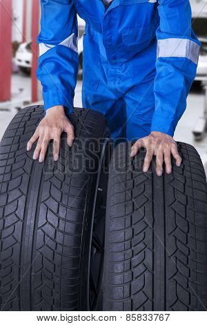 Two Tires With Mechanic In Workshop