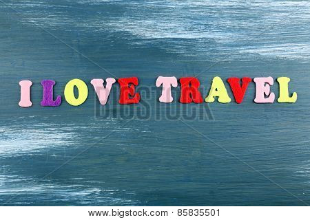 Inscription I love travel on wooden background
