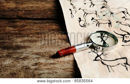 Rock paintings with magnifier on paper on wooden table close up