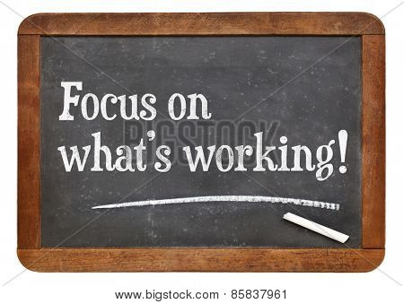 Focus on what is working. Motivational words on a vintage slate blackboard.