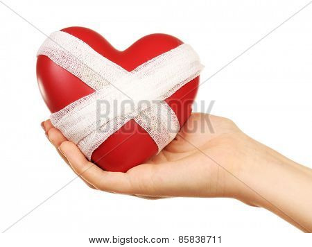 Female hand holding bandaged heart isolated on white