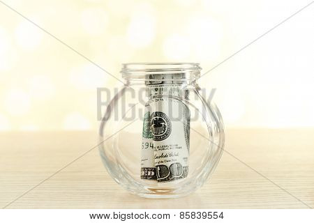 Dollars in glass bottle on bright blurred background