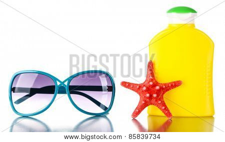 Bottle of suntan cream with sunglasses and sea star isolated on white