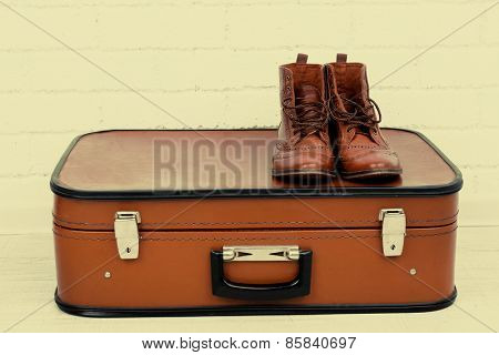 Vintage suitcase with male shoes on  floor on brick wall background