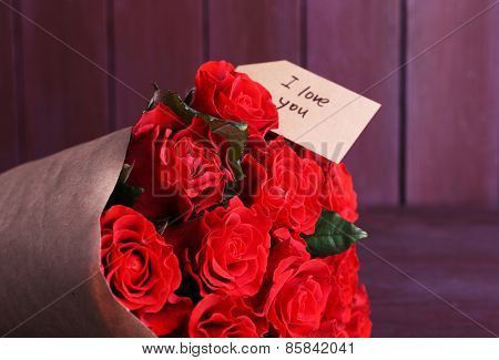 Bouquet of red roses with tag wrapped in paper on wooden background