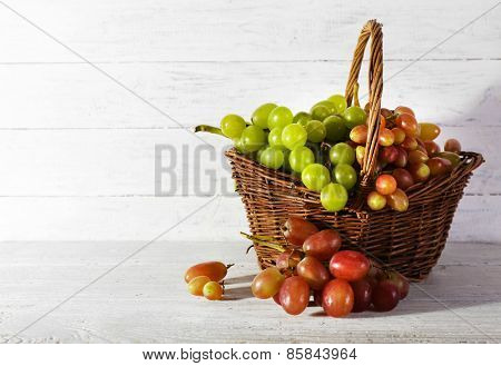 Grapes in basket on wooden background