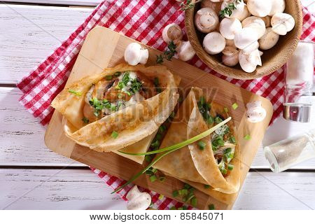 Pancakes with creamy mushrooms on cutting board on wooden table, top view