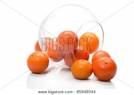 Ripe tangerine orange fruit in a glass vase transparent