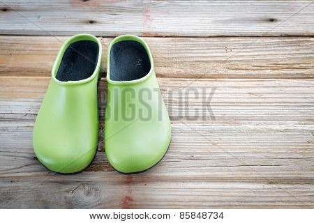 Green Gardening Shoes On Wood Surface