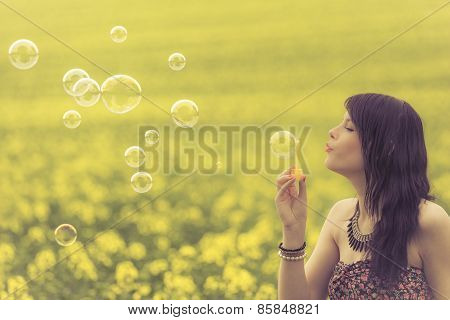 Beautiful Woman Blowing Many Soap Bubbles In Summer Nature