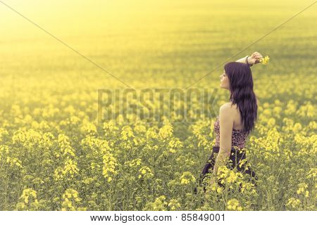Beautiful Woman In Meadow Of Yellow Flowers From Side Behind