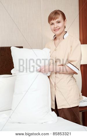 Maid changes bedclothes in hotel