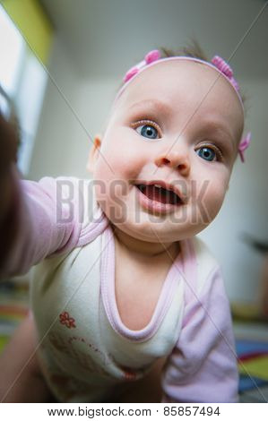 Adorable baby girl taking picture of herself, selfie.