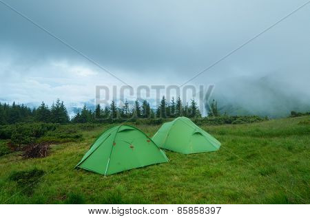 Camping in the mountains. Two green tourist tents. Evening landscape with cloudy sky.