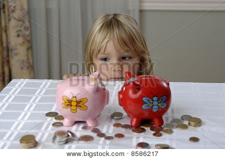 Preschool Girl And Piggy Banks
