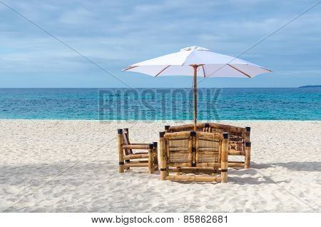 Tropical Resort View With Beach Table, Chairs And Umbrella On Exotic Sandy Beach
