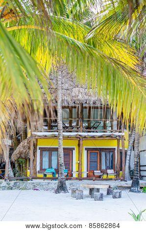 Tropical Villa View Through Palm Trees At Exotic Sandy Beach