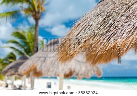 Tropical View Of Turquoise Lagoon With Beach Sunshades At Exotic Sandy Beach