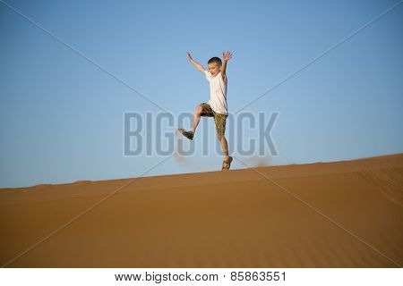 Little boy runs, jumps, plays on top of a sand dune in desert