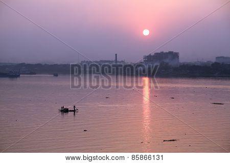 KOLKATA, INDIA - FEB 08: A boat crossing the river Ganges (aka River Hoogly) during sunset on February 08, 2014