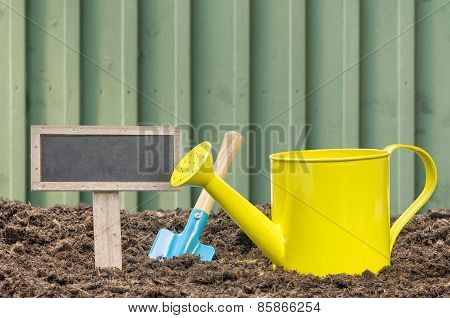 Watering Can And Shovel With An Empty Sign