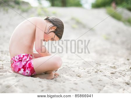 Little girl in pink shorts sitting on sand at the beach on hot summer day