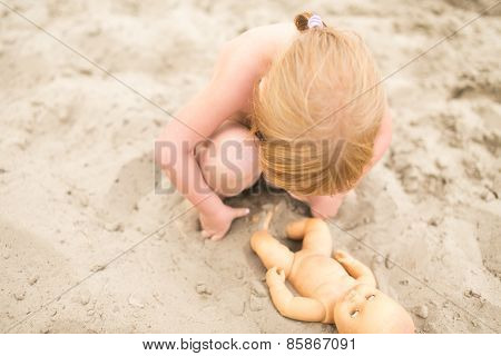 Toddler girl playing with baby doll at the beach on hot summer day