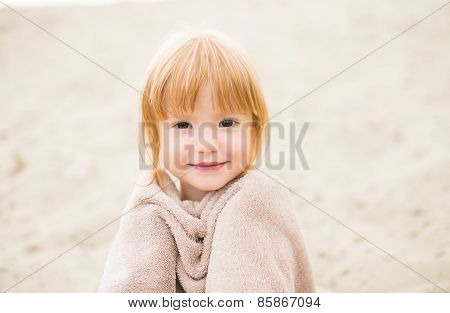 Toddler girl with red hair wrapped in a towel at the beach smiling at camera