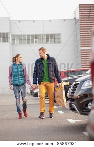 Couple Walking After Shopping Near Cars