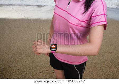 Sport Woman Wearing Smartwatch With Health Sensor On Beach Background