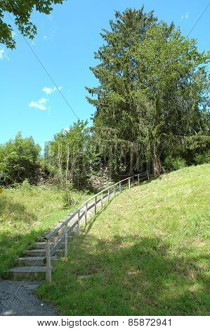 Stairs With Wooden Barrier On Hillside.