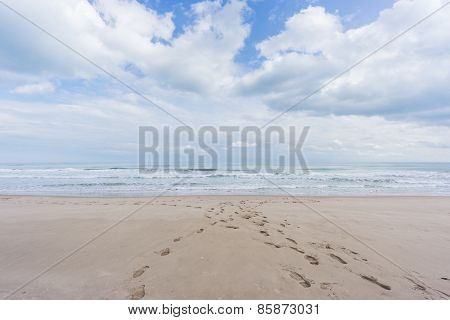 Footprints on the beach sand with sea and clouds