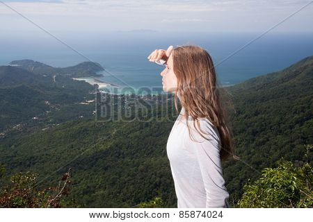 girl looks into the distance from the top of the mountain