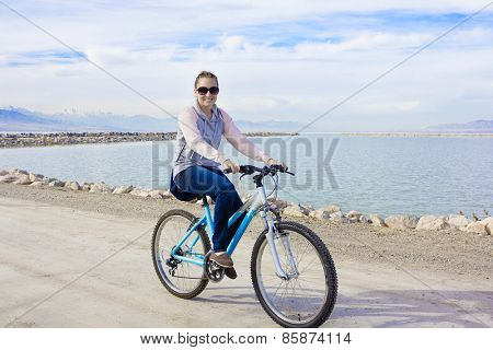 Healthy woman biking along the waterfront