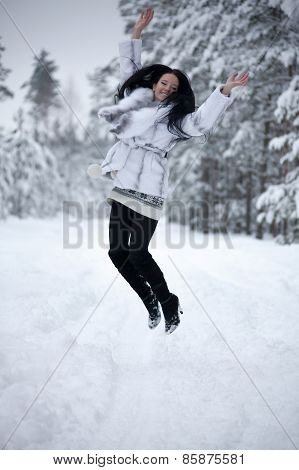 Young Woman Is Jumping In Winter Forest