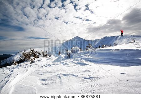 Man in a red jacket on the mountain looking at the snow-covered