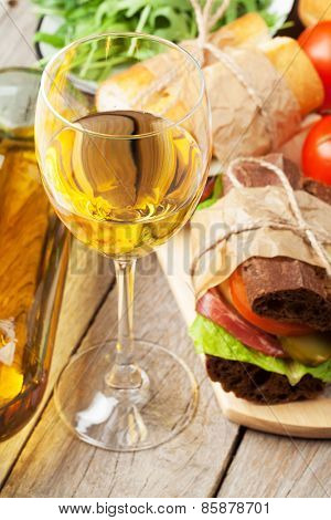 White wine glass, sandwiches and salad on wooden table