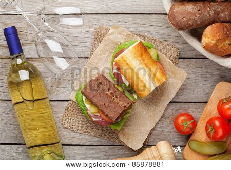 Two sandwiches with salad, ham, cheese and tomatoes with white wine on wooden table. Top view