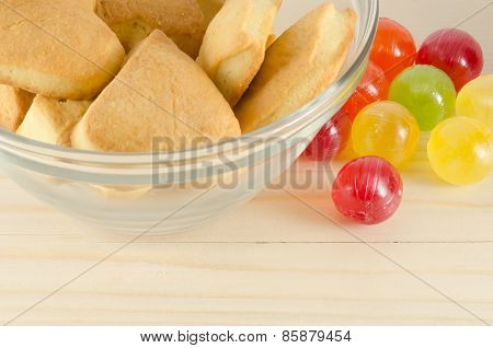 Colorful candies and cookies on wooden background