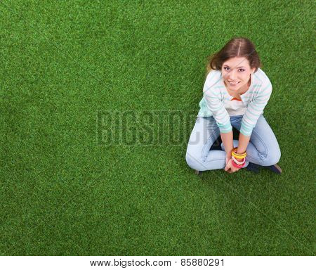 Young woman sitting  on green grass   .