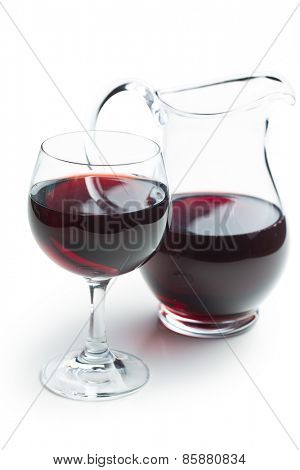 glass of red wine with pitcher on white background
