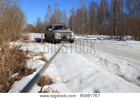 Icy Road In Forest, Cable Runs From Winch Stuck Vehicle.